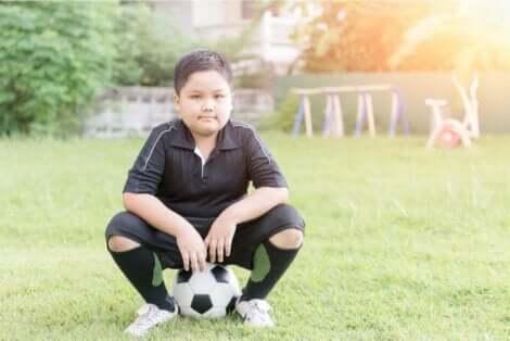 طفل جالس على كرة قدم